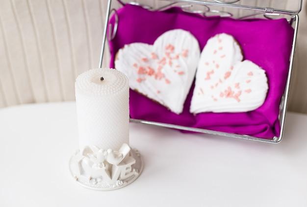 Kaars en koekjes in de vorm van een hart op een roze servet