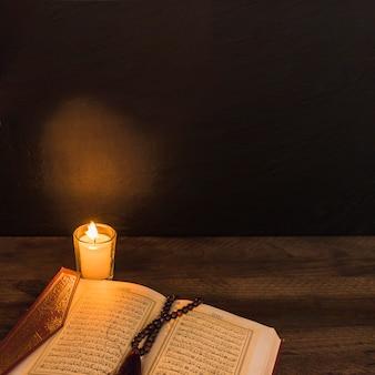 Kaars en koran met parel in donkere ruimte