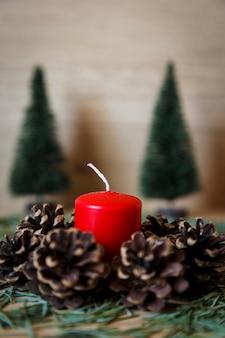 Kaars naast een reeks denneappels en sparren als kerstmisdecoratie