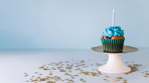 Kaars op cupcake over cakestand tegen blauwe achtergrond