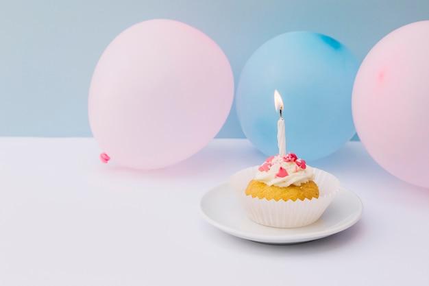 Kaars op cupcake over plaat met roze en blauwe ballonnen