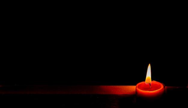 Kaars op donkere achtergrond. eenzaam rustig branden.