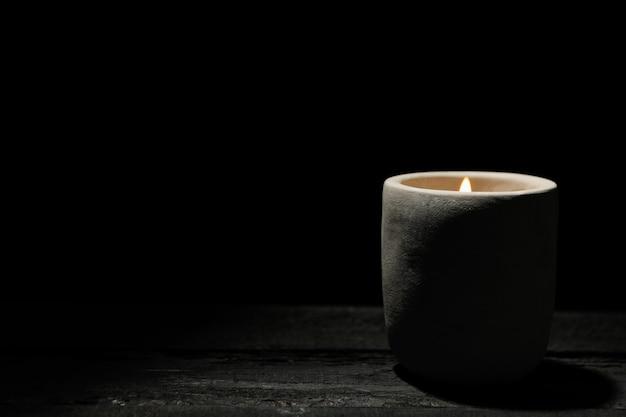 Kaars op houten tafel op zwart