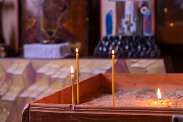 Kaarsen branden in de orthodoxe kerk voor het icoon