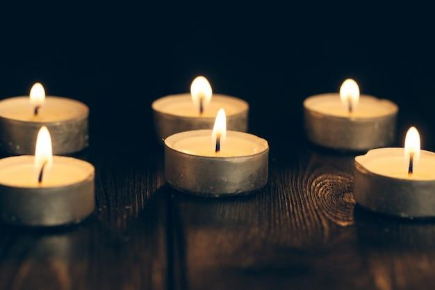 Kaarsen branden in het donker over zwart. herdenking.