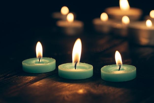 Kaarsen branden in het donker over zwart.