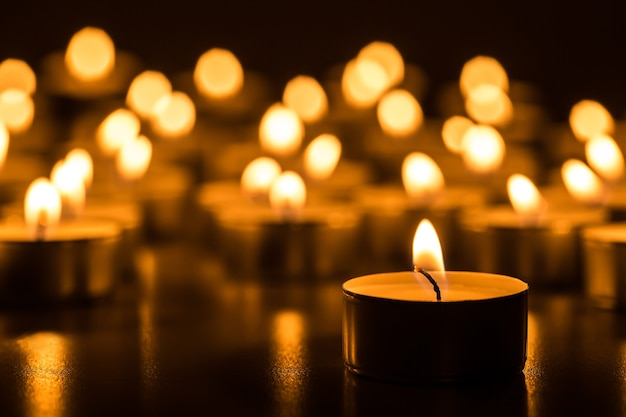 Kaarsen branden. kerstkaarsen die 's nachts branden. abstracte kaarsenachtergrond. gouden licht van kaarsvlam.
