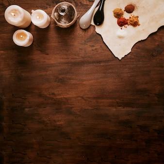 Kaarsen dichtbij fles en ingrediënten op perkament