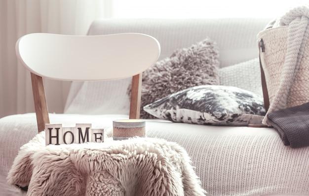 Kaarsen, een vaas met bloemen met houten letters van het huis op houten witte stoel. bank en rieten mand met kussens op de achtergrond.