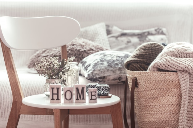 Kaarsen, een vaas met bloemen met houten letters van het huis op houten witte stoel. bank en rieten mand met kussens
