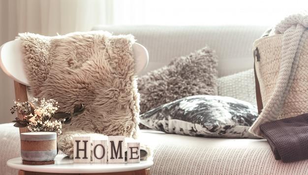 Kaarsen, een vaas met bloemen met houten letters van het huis op houten witte stoel. bank en rieten mand met kussens.