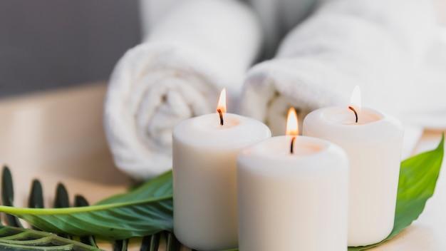 Kaarsen en bladeren in de buurt van handdoeken