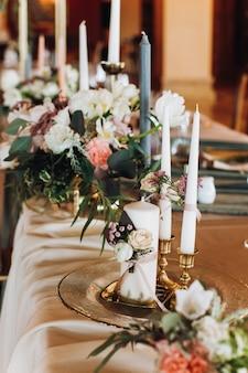 Kaarsen en boeketten op de versierde tafel