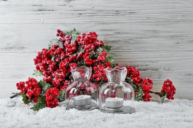Kaarsen en tak van hulstbessen in een sneeuw over houten achtergrond, stilleven