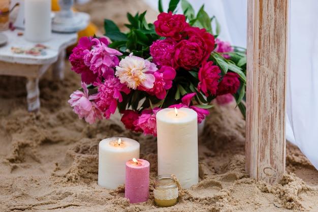 Kaarsen en verse bloemen op het strand