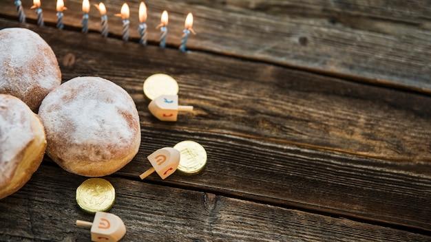 Kaarsen in de buurt van donuts en hanukkah-symbolen