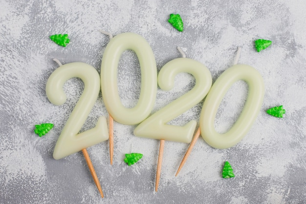 Kaarsen in de vorm van nummer 2020 als een symbool van het nieuwe jaar naast kerstvormig fonkelend snoep op een grijze tafel. bovenaanzicht, platliggend