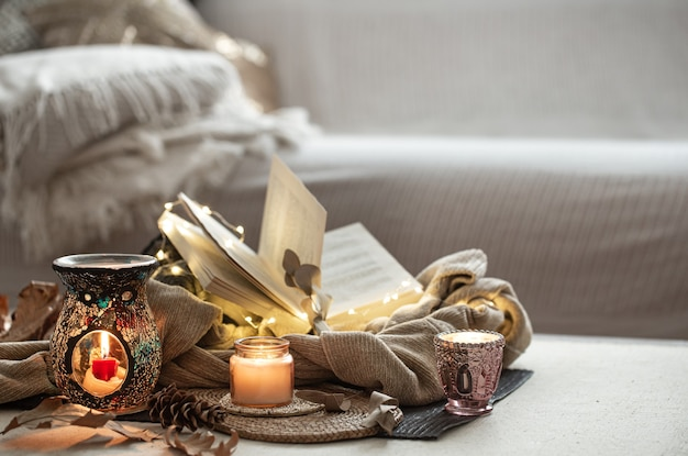 Kaarsen in kandelaars, boek, trui, slinger op de lichte ruimte van de woonkamer.
