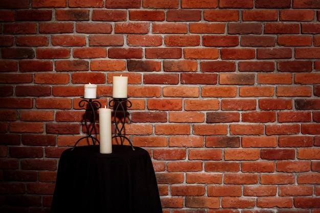 Kaarsen op tafel over bakstenen muur
