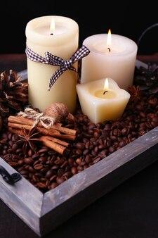 Kaarsen op vintage dienblad met koffiebonen en kruiden, stoten op houten tafel, op donkere ondergrond