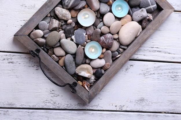 Kaarsen op vintage dienblad met zee kiezels, op houten achtergrond