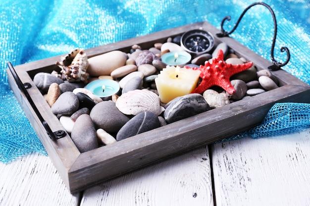 Kaarsen op vintage dienblad met zee kiezels, zeesterren en zeeschelpen op houten achtergrond