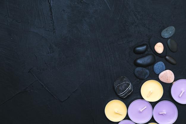 Kaarsen, orchideebloemen en keien op een zwarte steenachtergrond. bovenaanzicht, kopieer ruimte. spa concept, plat leggen.