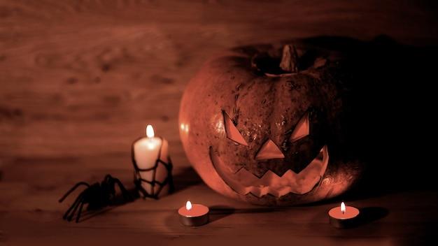 Kaarsen, pompoenen en een spin op een houten achtergrond .photo met kopieerruimte