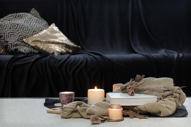 Kaarsen, trui en boek op tafel tegen de achtergrond van een donkere bank.