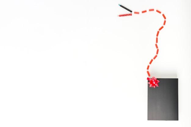 Kaarsen verbonden met snoepjes aan zwarte geschenkdoos met rode decoratieve strik op witte achtergrond
