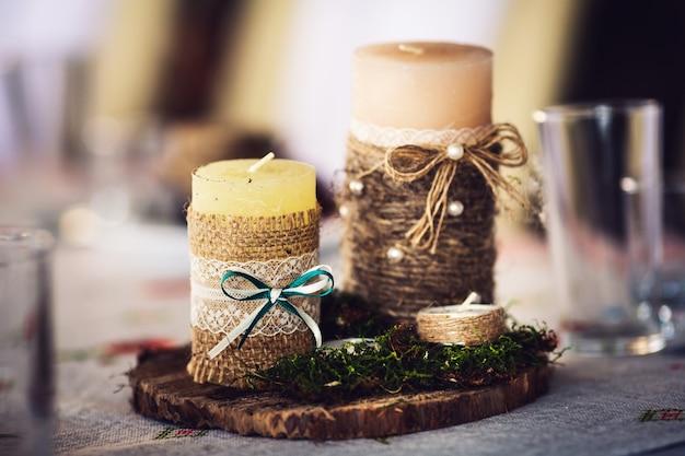 Kaarsen verpakt in jute en versierd met een strik, kant en mos op een houten standaard.