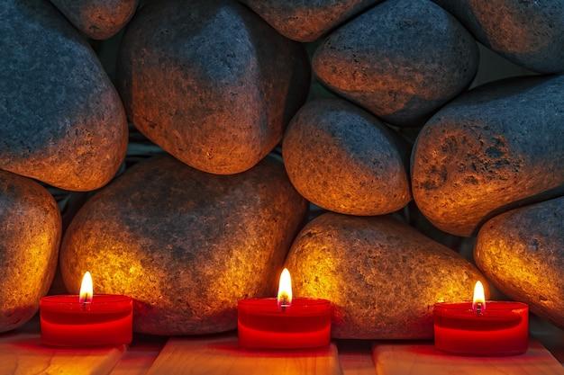 Kaarsen worden aangestoken op de achtergrond van de saunastenen. voorbereiding voor de ceremonie badhuis