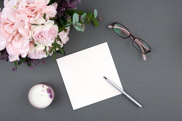 Kaart en pen met boeket rozen op grijs