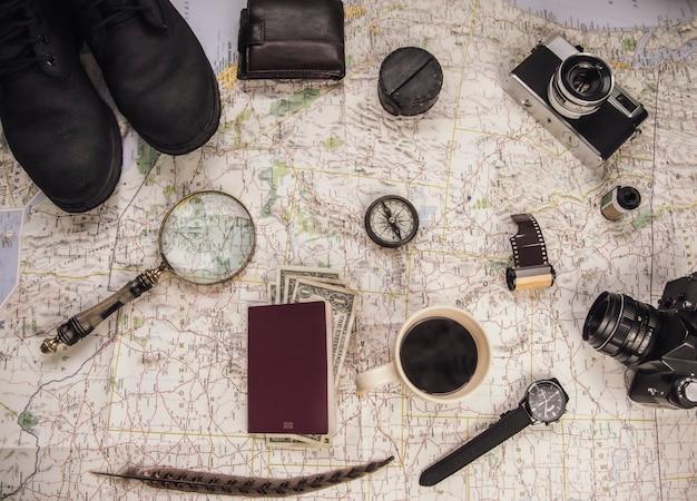 Kaart, fotocamera's, haspels, zonnebril, kompas, vergrootglas, paspoort, geld, portemonnee, laarzen en pen