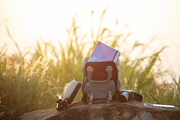 Kaart in rugzak, mobiele telefoon met oortelefoon en hoed op berg met een reiziger.