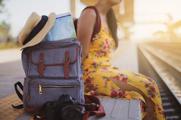 Kaart in rugzak, mobiele telefoon met oortelefoon en hoed op het treinstation met een reiziger. zon set, reisconcept.