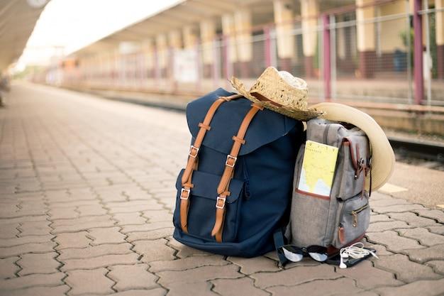 Kaart is in een vintage tas met hoeden, zonnebrillen, mobiele telefoons en koptelefoon op het treinstation