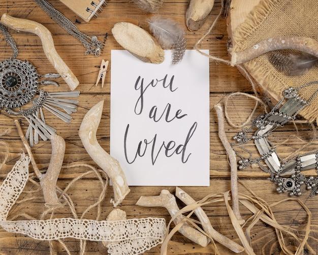 Kaart met de handgeschreven tekst you are loved met bohemian versieringen rondom bovenaanzicht op een houten tafel