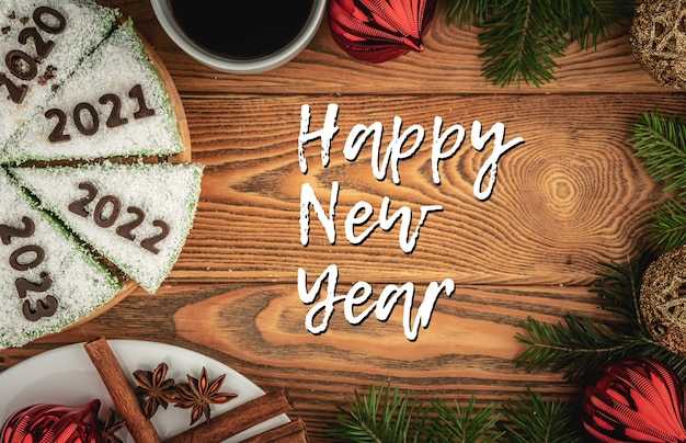 Kaart met feestelijke cake versierd met cijfers ter aanduiding van de jaren 2020, 2021, 2022, 2023 gemaakt van chocolade en het opschrift happy new year. bovenaanzicht.