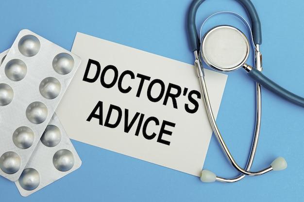 Kaart met tekst - doktersadvies, pillen en stethoscoop.