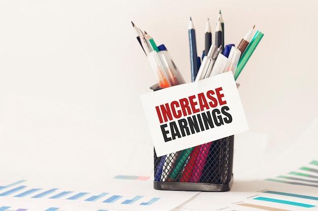 Kaart met tekst verhoging van de inkomsten op de pennenbak op kantoor. diagram