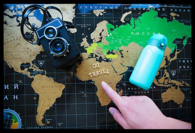 Kaart van de wereld in het russisch. de vinger van het meisje wijst naar verschillende uithoeken van de wereld. Premium Foto