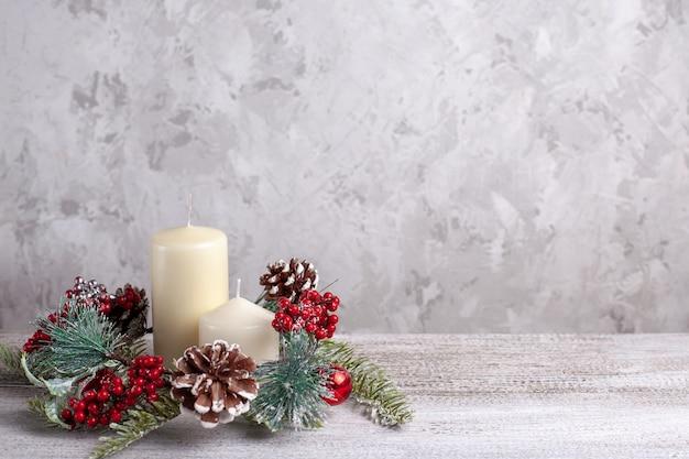 Kaart van twee beige vanille dikke kerstkaarsen en een krans van kegels, rode bessen op een houten achtergrond.