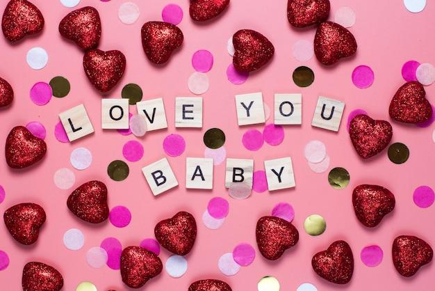 Kaart voor valentijnsdag. op een roze houten letters bekleed met i love you baby. grappige gefeliciteerd. plat lag, bovenaanzicht.