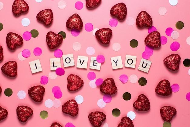 Kaart voor valentijnsdag. op een roze houten letters bekleed met ik hou van jou.
