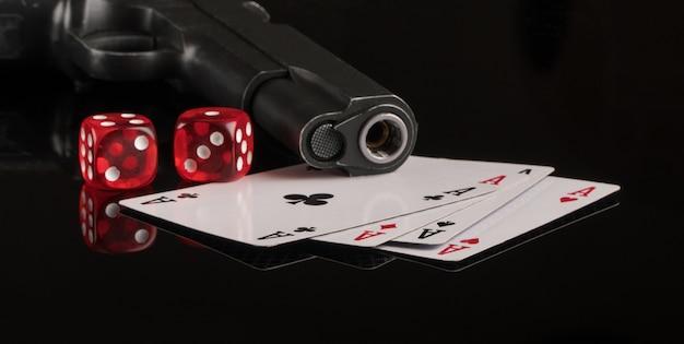 Kaarten dobbelstenen en een pistool op een zwarte achtergrond gokken en entertainment casino en poker