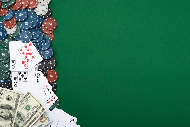 Kaarten en pokerfiches met amerikaanse dollarbiljetten op een groene achtergrond.