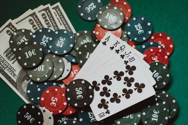 Kaarten met een royal flush op een stapel chips en geld dollars