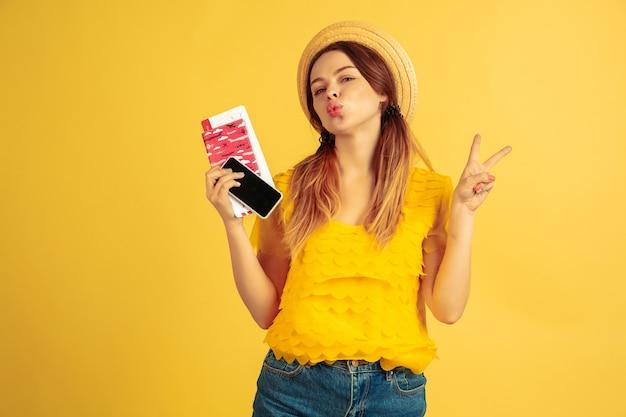 Kaartjes, gadget. het portret van de kaukasische vrouw op gele studioachtergrond. mooi vrouwelijk model in hoed. concept van menselijke emoties, gezichtsuitdrukking, verkoop, advertentie. zomer, reizen, resort-concept.