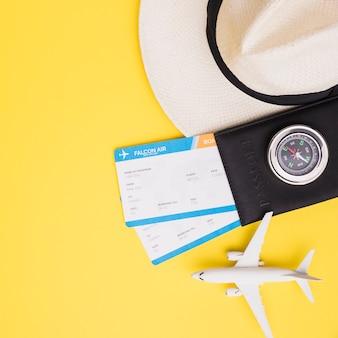 Kaartjes met paspoort, hoed en vliegtuig